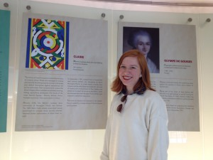 Claire stands in front of panels from the UN Women and Slavery exhibition.